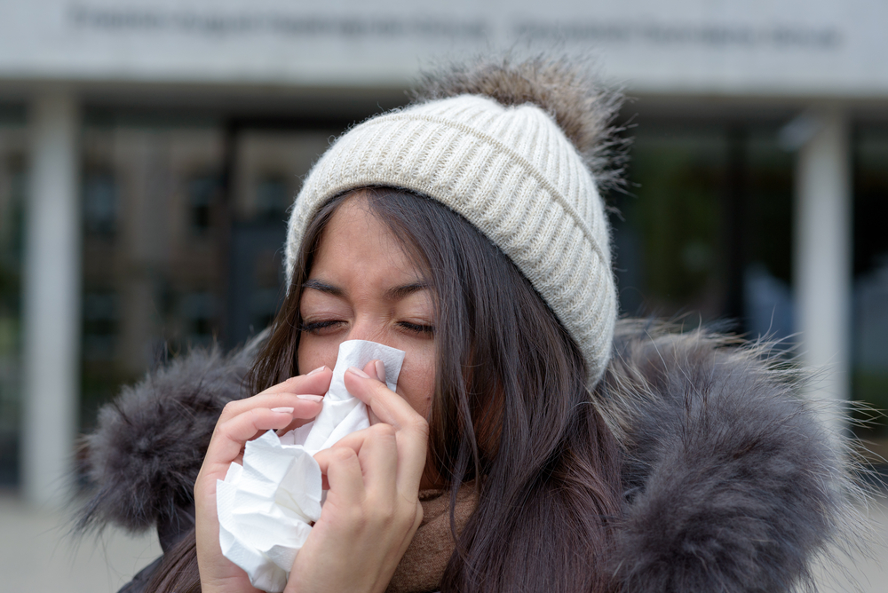 A young woman fights off the flu, via Shutterstock