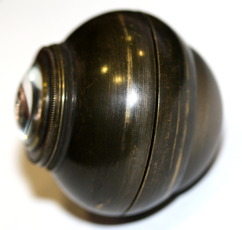 "Part of the practice eye from the British Optical Association Museum's collection. The ""cornea"" appears at the far left and can be unscrewed and replaced with a different cornea. Alternatively, a ""corneal cap"" can be affixed to the cornea piece to mimic a spectacle lens. Courtesy of The College of Optometrists"