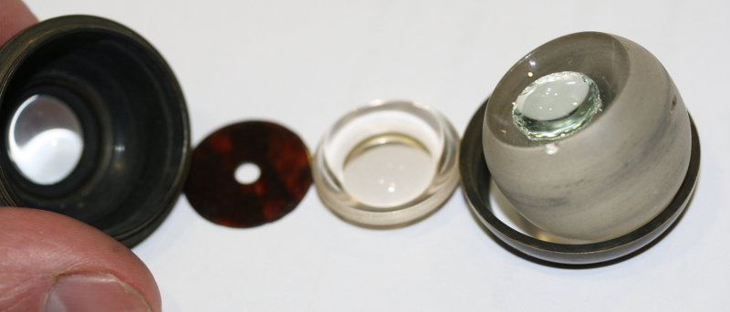 "The inner components of the practice eye in the British Optical Association Museum's collection. The ""cornea"" appears at far left, followed by a brown, artifcial ""iris"" (with a glass support used to hold it in place). The ""lens"" is the tiny glass disk nestled inside a larger glass chunk, which serves as the eye's ""vitreous jelly."" Courtesy of The College of Optometrists"