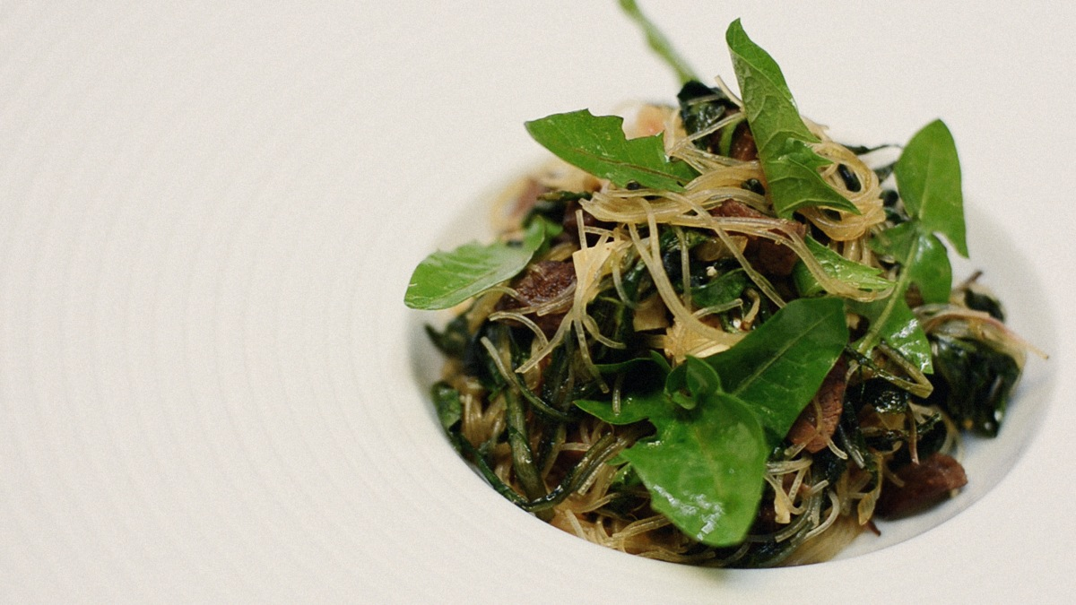 Dandelion leaves with braised beef and clear noodles. Photo by Tama Matsuoka Wong