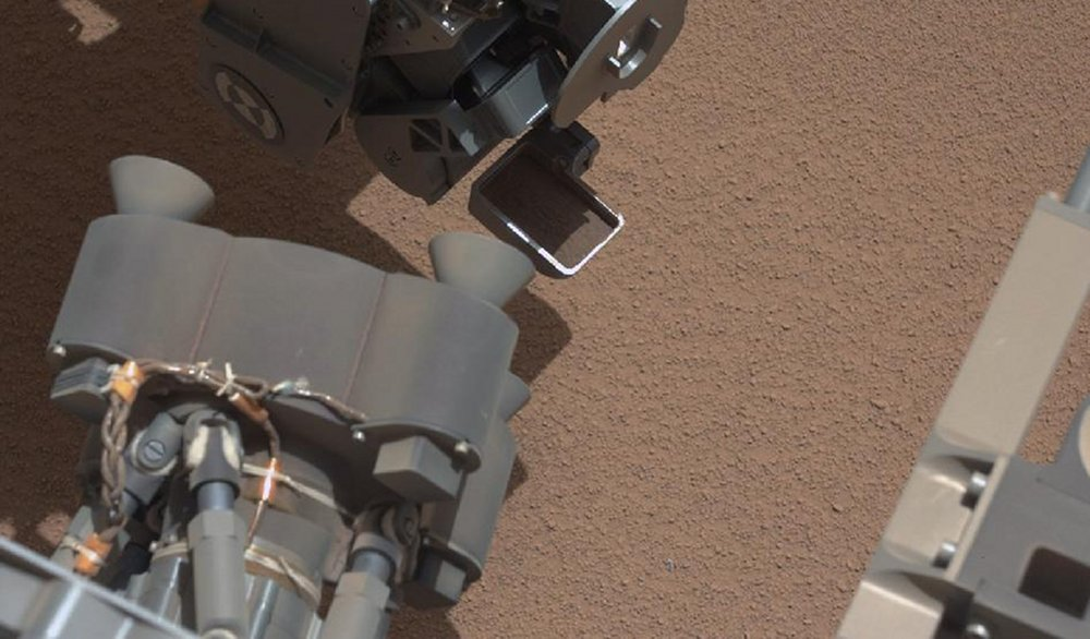 This image from the right Mast Camera (Mastcam) of NASA's Mars rover Curiosity shows a scoop full of sand and dust lifted by the rover's first use of the scoop on its robotic arm. In the foreground, near the bottom of the image, a bright object is visible on the ground. The object might be a piece of rover hardware. Image courtesy of NASA/JPL-Caltech/LANL