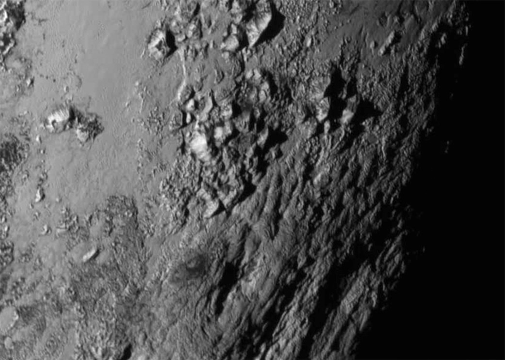 New close-up images of a region near Pluto's equator reveal a giant surprise: a range of youthful mountains rising as high as 11,000 feet (3,500 meters) above the surface of the icy body. Image credit: NASA-JHUAPL-SwRI