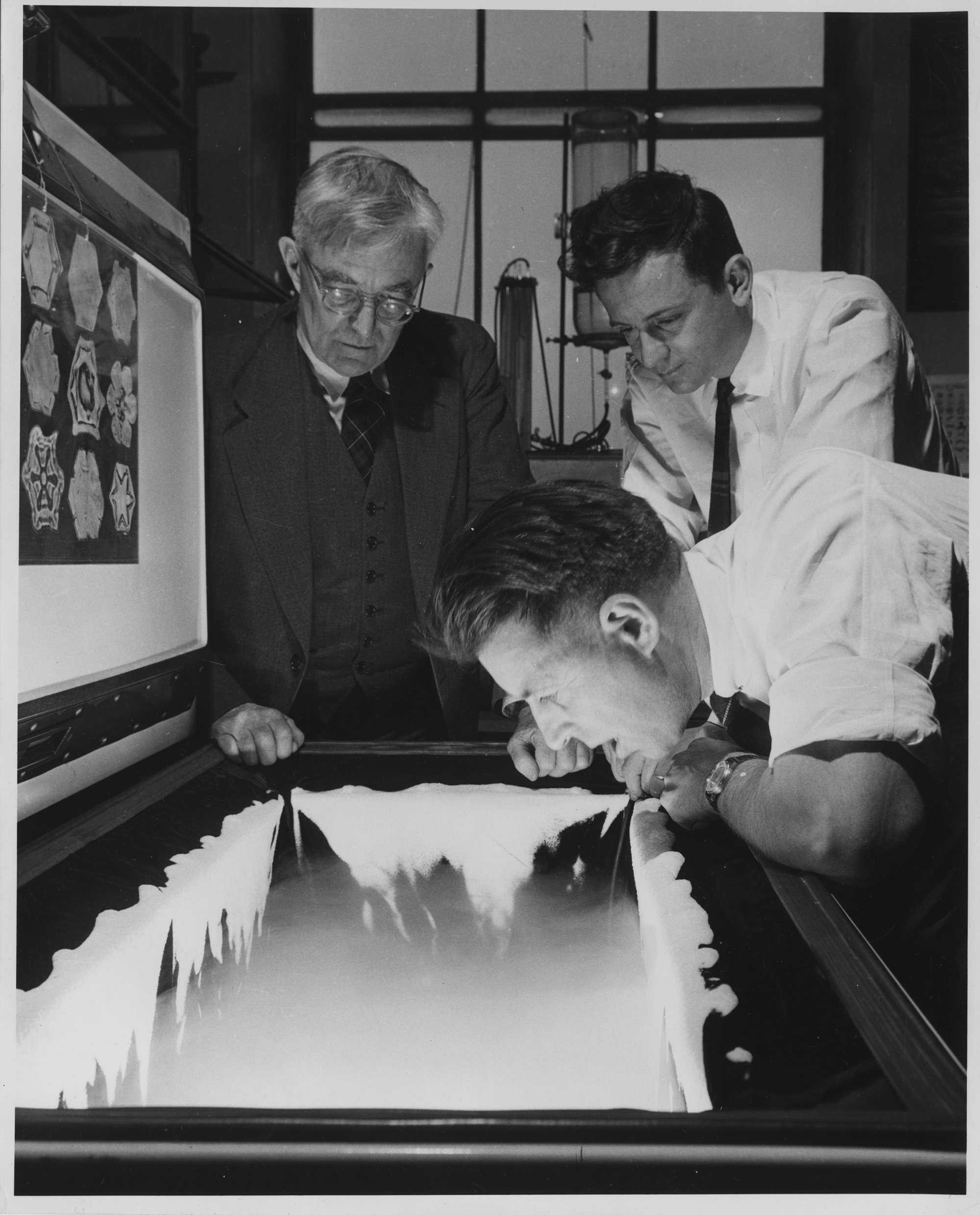 GE scientist Vincent Schaefer breathes a cloud into a freezer, as colleagues Irving Langmuir and Bernard Vonnegut (Kurt Vonnegut's brother, at center) look on. He'll nucleate this laboratory-made cloud with dry ice to create snow. Photo by GE News Bureau