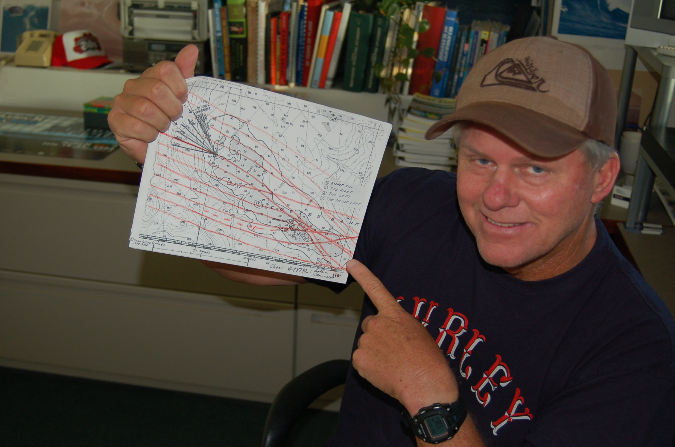 Sean Collins with a hand-drawn map he created years ago to calculate the swell, reef, and bathymetry of the Cortes Bank, a seamount 100 miles off the coast of California where huge waves are surfed. Photo by Chris Dixon