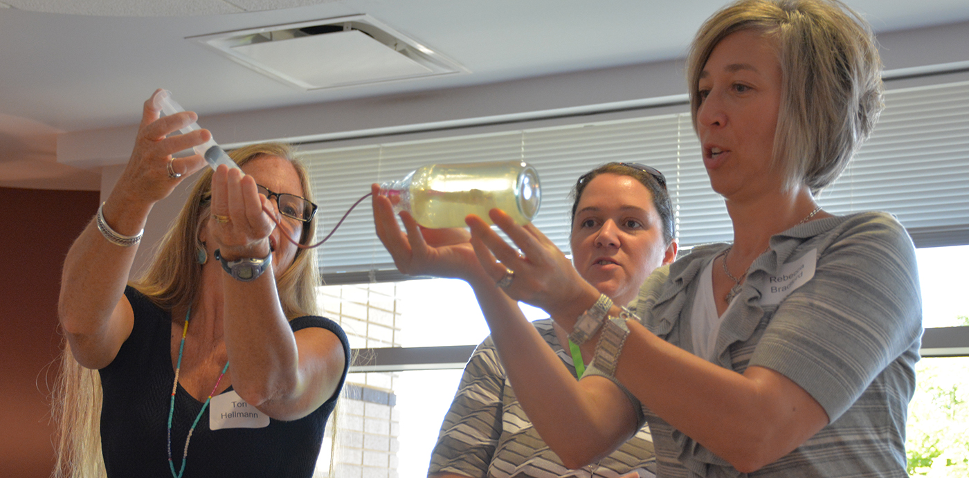 Tori Hellmann, Shelly Grandell, and Rebecca Bradford demonstrate how to frack gelatin in a bottle using a horse catheter and syringe. The borehole into the gelatin is held open with a wide drinking straw. plaster of Paris is used to simulate fracking fluid. (Photo: L.S. Gardiner)