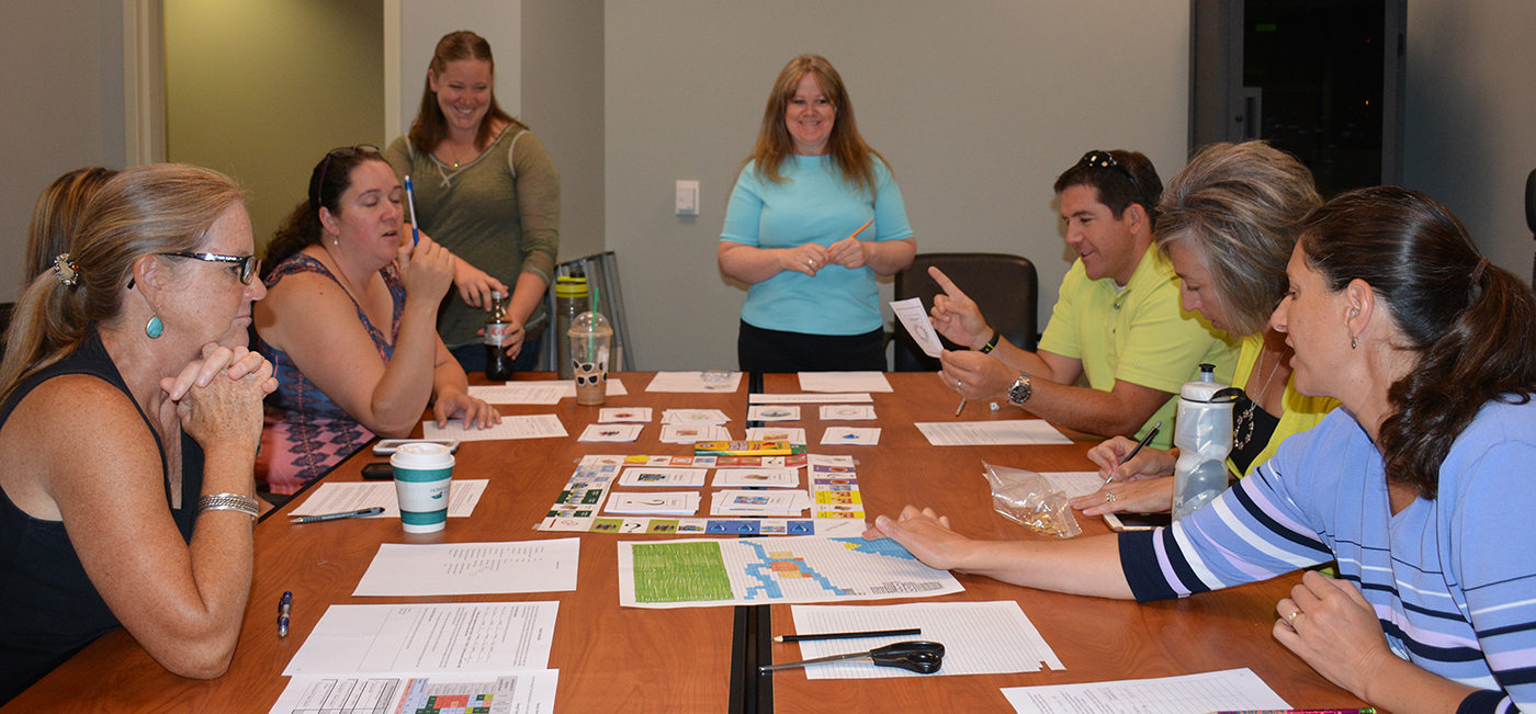 The eight AirWaterGas Teachers-in-Residence test the Boomtown Game. (Photo: L.S. Gardiner)