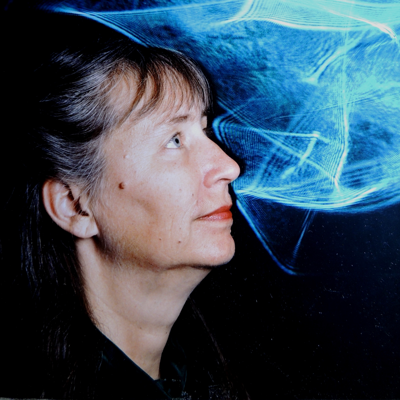 "Dr. Elsa Garmire in front of one of her laser light artworks in 1992. Dr. Garmire's artistic experiments with lasers in the early seventies inspired the laser light show known as ""Laserium."" Photo by Patricia Tryforos"