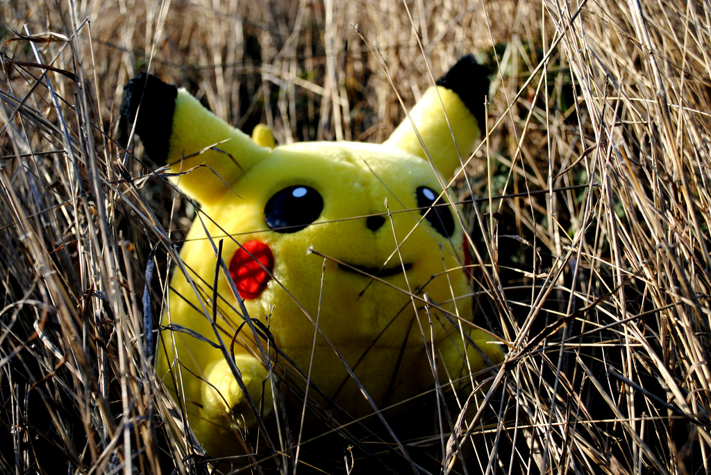 Pikachu, from the game Pokemon, crouches in the grass. Credit: Sadie Hernandez/Flickr [CC-BY