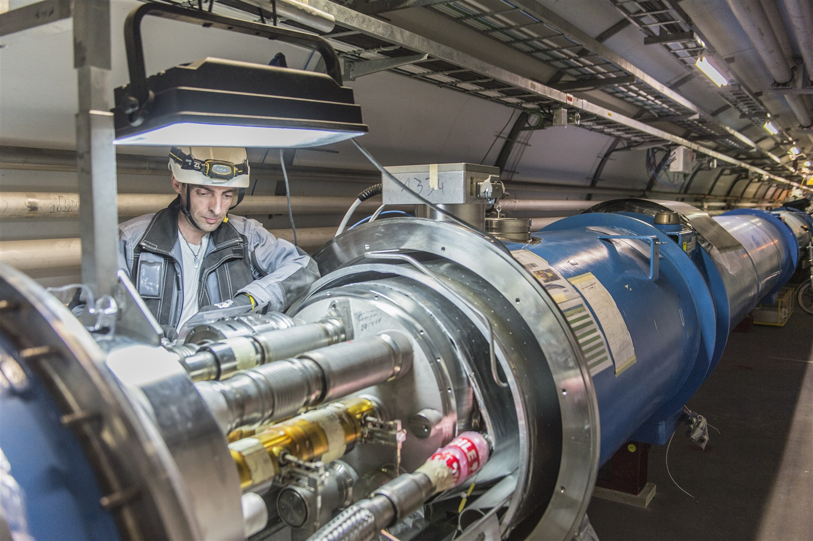 A CERN engineer inspecting machinery. Credit: CERN