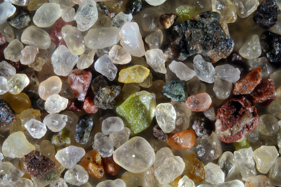 Sand found in Calumet, in Michigan's Upper Peninsula. The pistachio-green grain in the center is epidote, and its blue-green neighbor is diopside. The rounded grain right-of-center is colored pink with copper. The clear grains are quartz; some are incredibly rounded. Magnified 125 times. Credit: Gary Greenberg/The Secrets of Sand