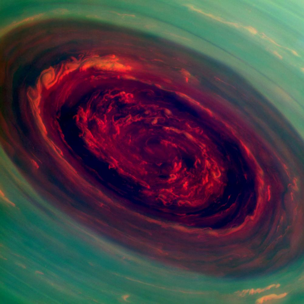 The spinning vortex of Saturn's north polar storm resembles a deep red rose of giant proportions surrounded by green foliage in this false-color image. Measurements have sized the eye at a staggering 1,250 miles across with cloud speeds as fast as 330 miles per hour. Credit: NASA/JPL-Caltech/Space Science Institute