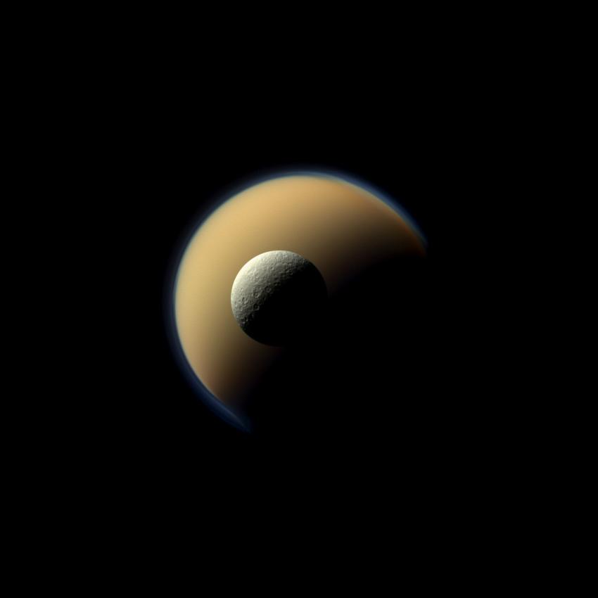 Saturn's largest and second largest moons, Titan and Rhea, appear to be stacked on top of each other in this true-color scene. Credit: NASA/JPL-Caltech/Space Science Institute