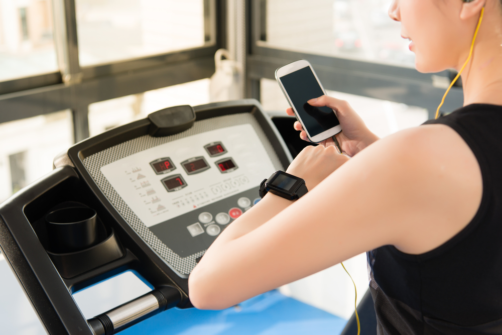 A woman checks her phone on the treadmill, via Shutterstock