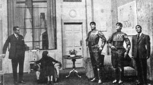 old black and white photo in a living room with three stiff robot people with two regular humans