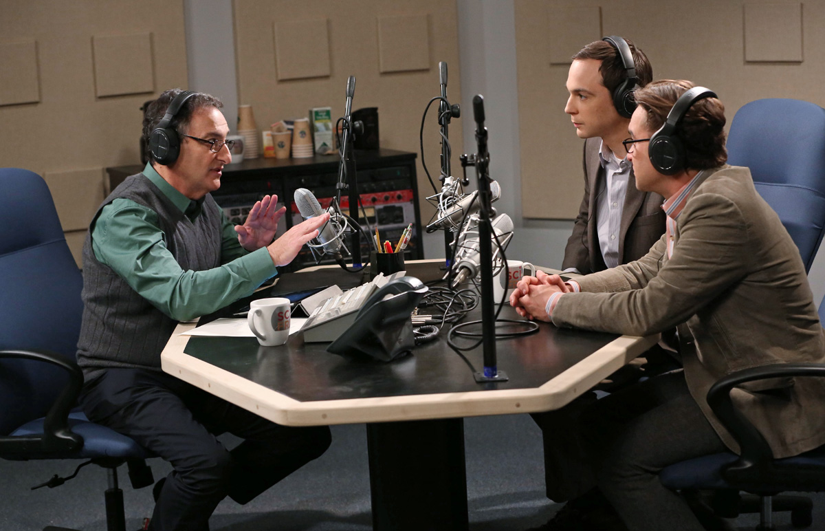 three people sitting around desk with microphones in a radio studio