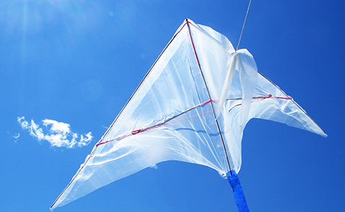 Kite made out of plastic bags flies against a blue sky on a windy day