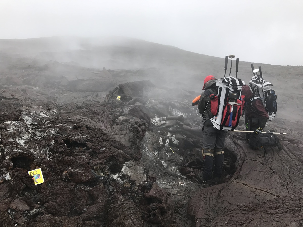 two people fully clothed in extreme hiking gear with large backpacks with antennas coming out stand on a black, molten landscape with pockets of steam seeping from the ground