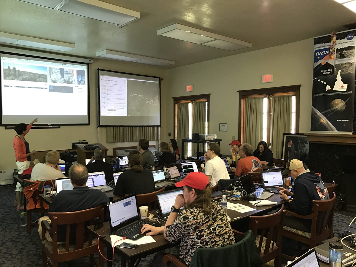 A dozen or so people sit in a room at three rows of long desks with computers. at the front of the room is an instructor gesturing at two projected images on the wall