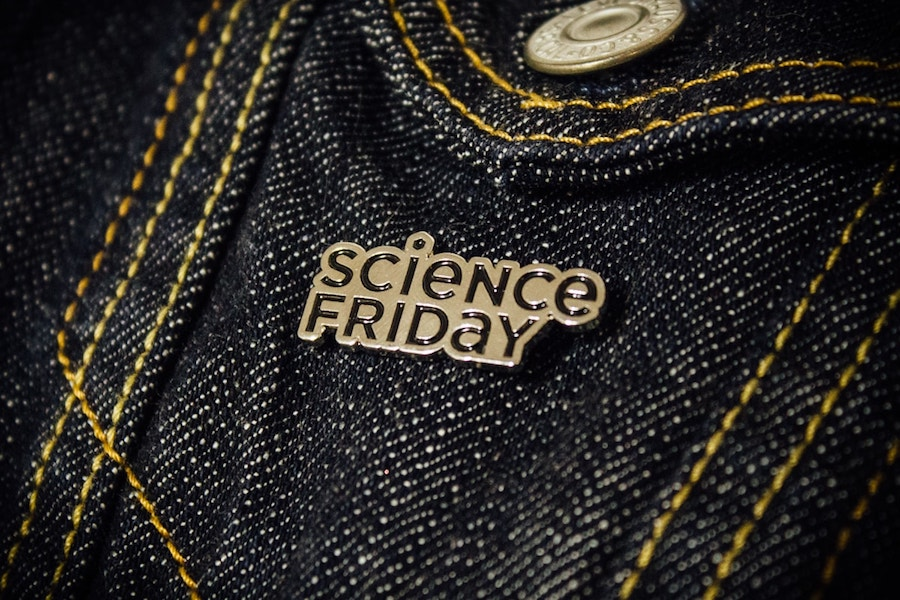 a silver science friday pin on a jean jacket