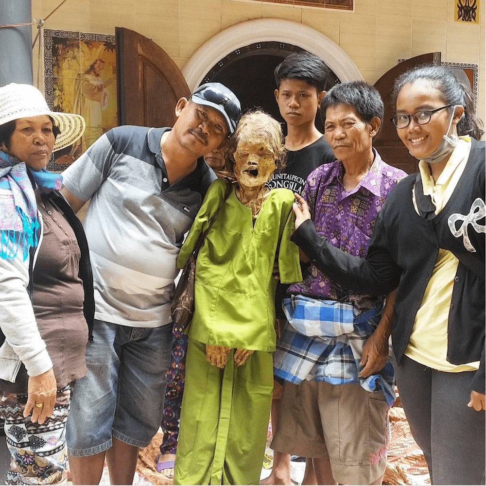 family in indonesia poses with mummified loved one