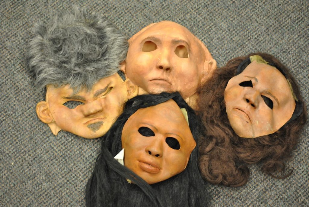 an array of skin-toned research masks with different colored hair