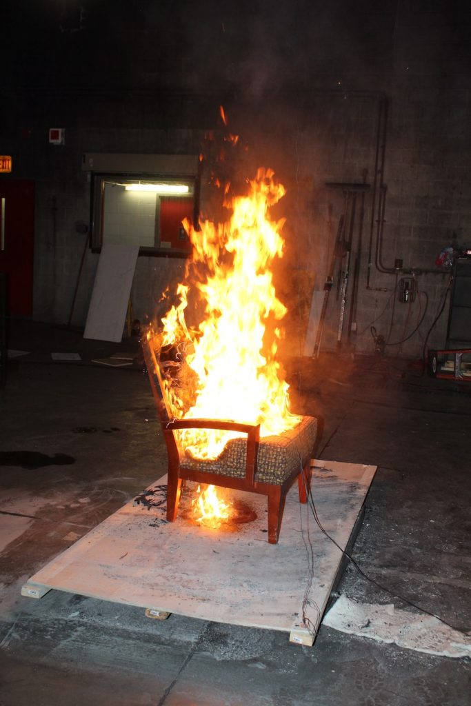 a wooden chair with a polyurethane foam pad on fire