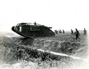 WWI tank in field with soldiers