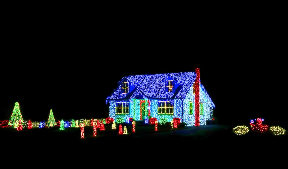 Intense bright colors LED Christmas light show and display on a house and its yard for festive holiday illuminations on a black night