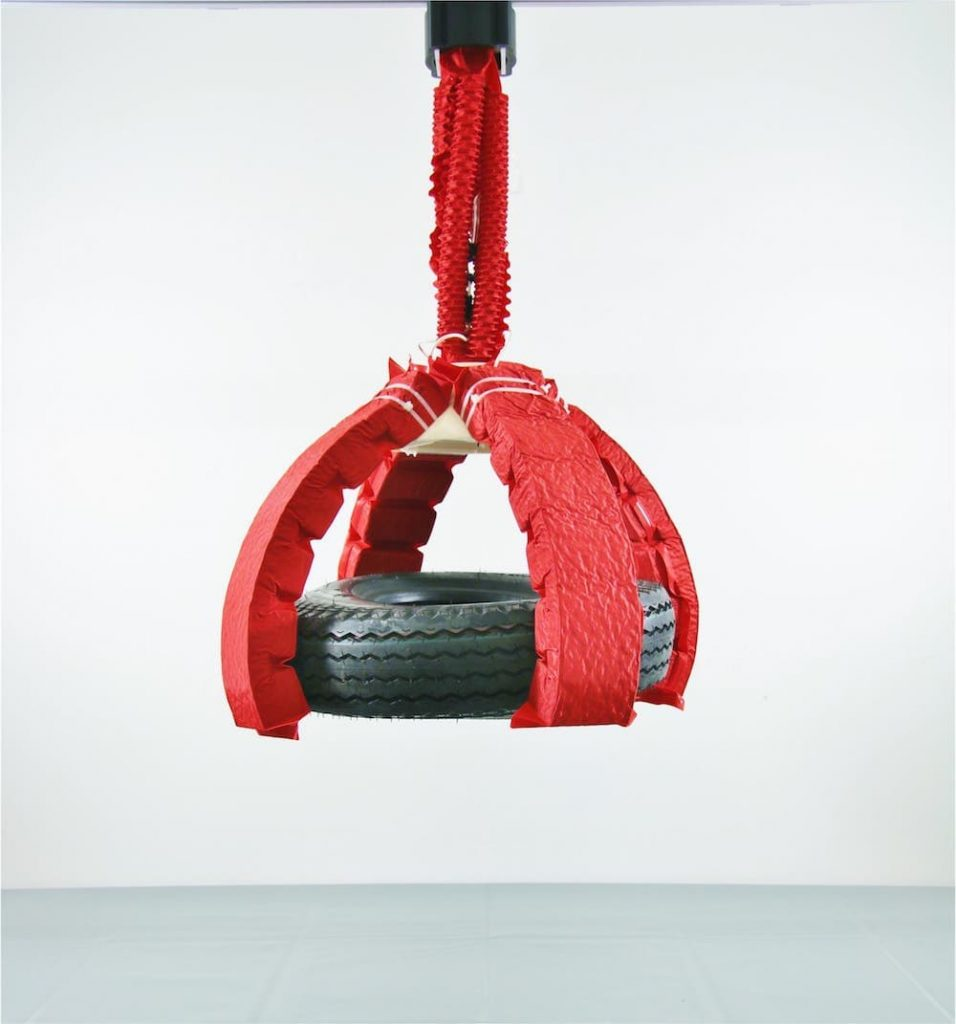 red soft robot arm and claw holding a tire