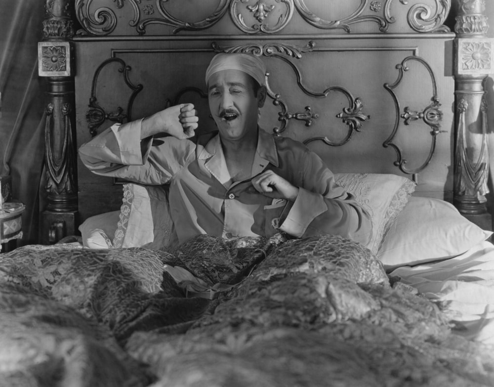 black and white man in bed with cap yawning