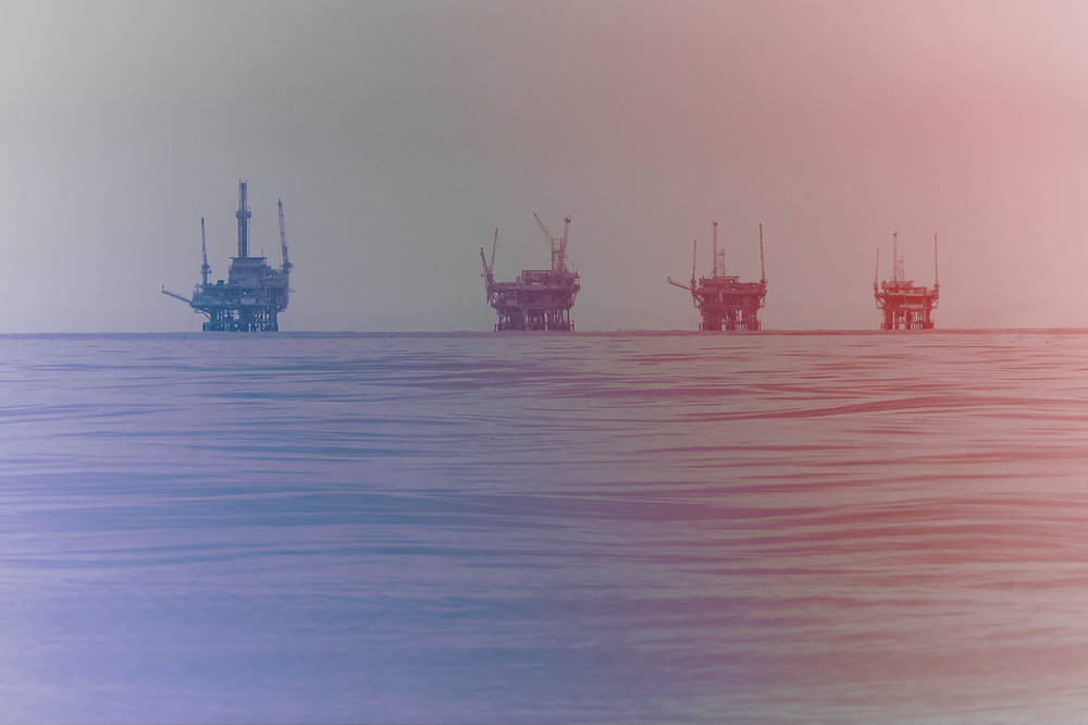 four oil rigs in a row in the ocean