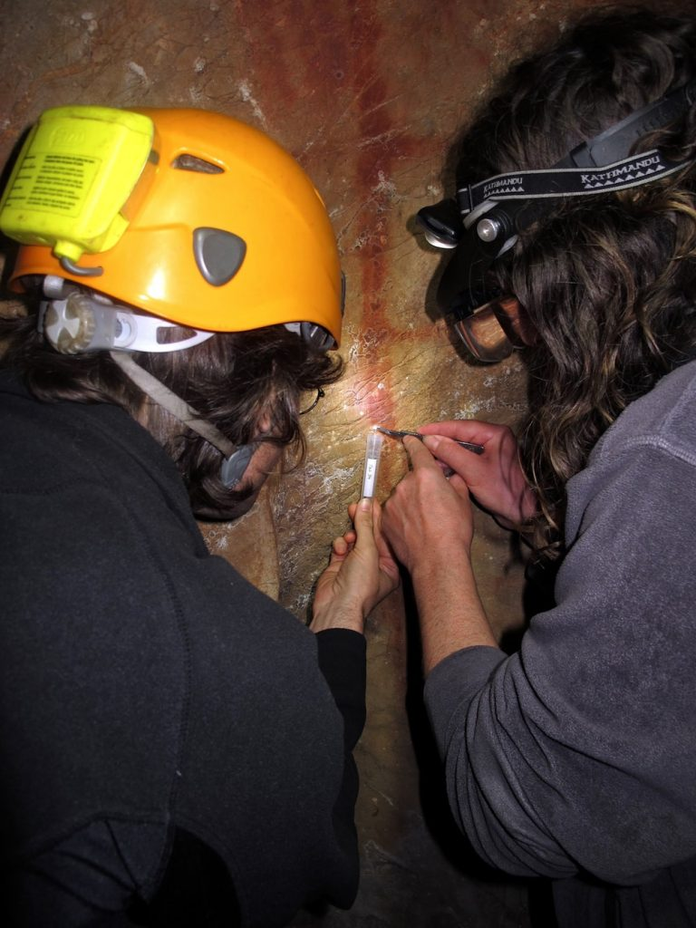 researchers in hard hats taking sample off cave wall