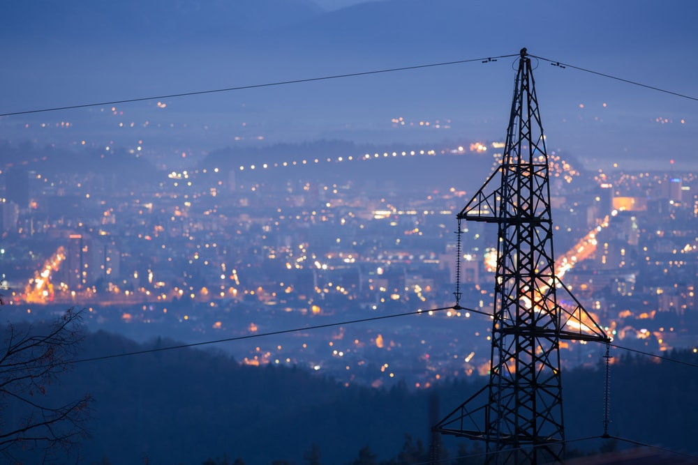 power lines with city lights in the background