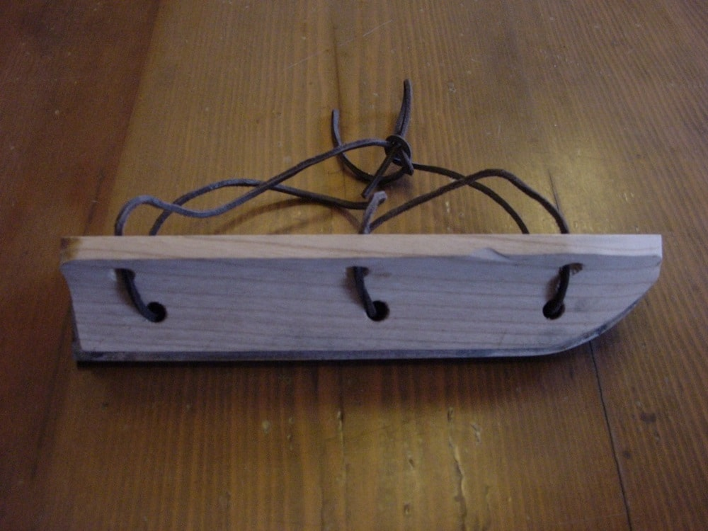 thick wooden skate with strings and thin blade