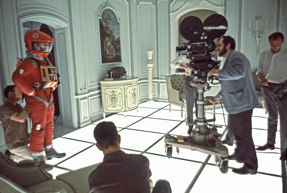 the film crew sets up in an opulent hotel room with one of the astronauts standing in his suit