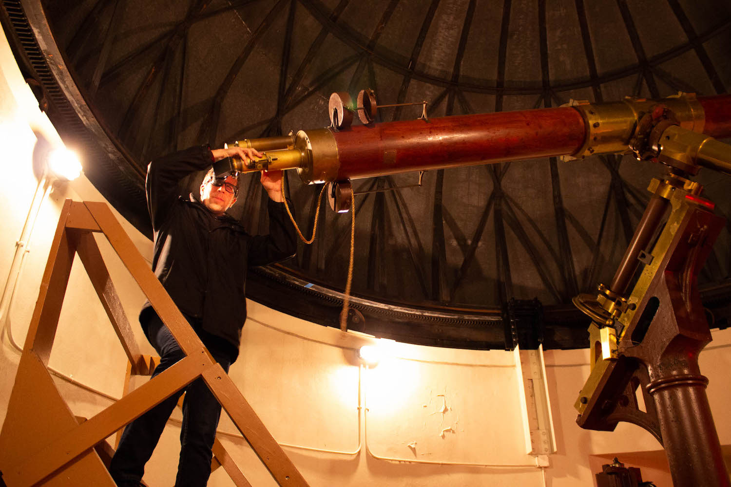 a man looking through a large wooden telescope in an observatory