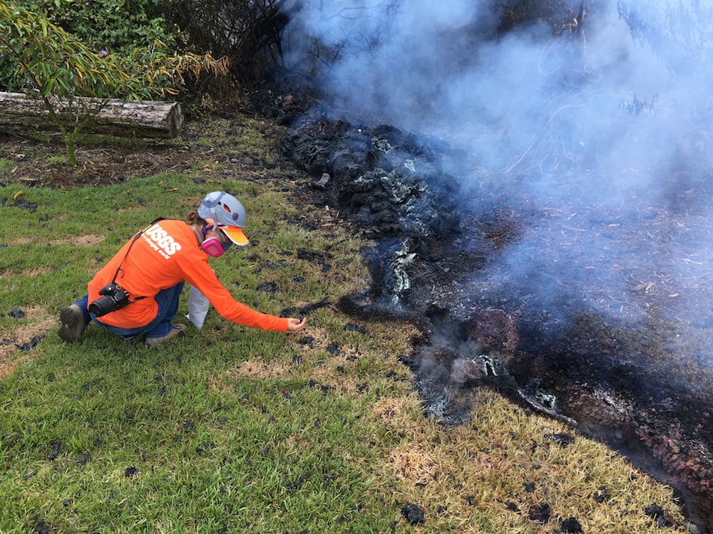 person with gas mask carefully samples lava
