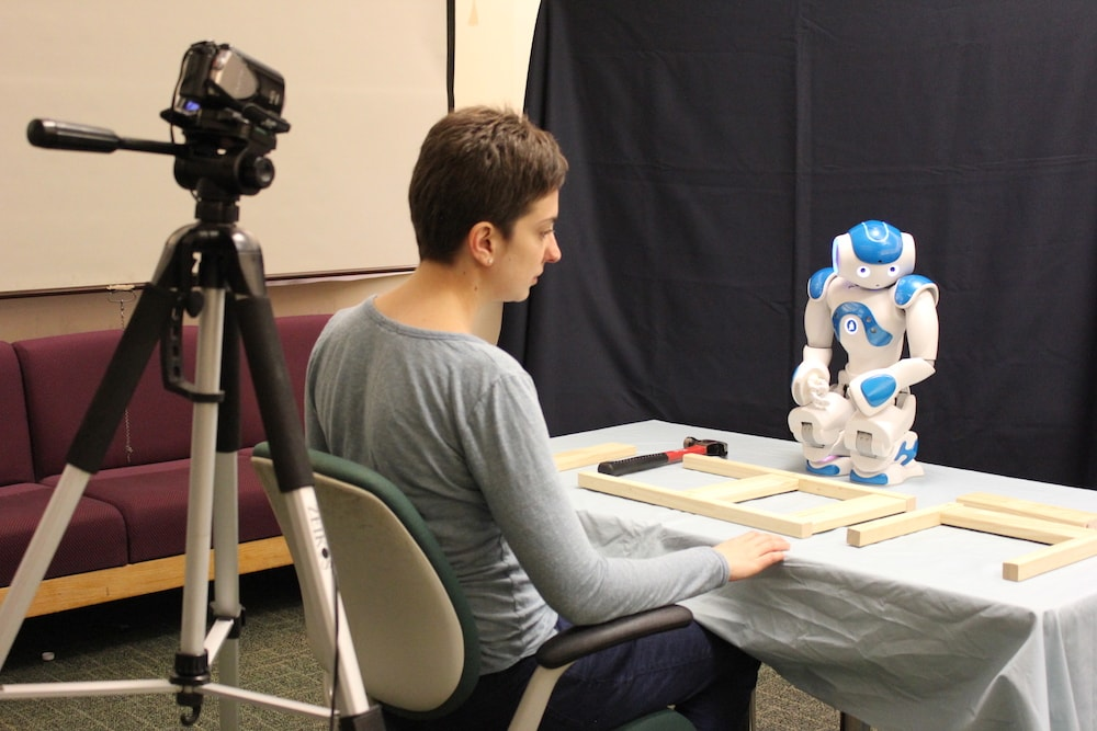 a researcher studying a small humanoid robot