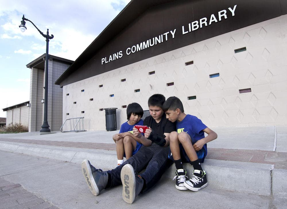 three children sitting in front of a library playing a handheld video game