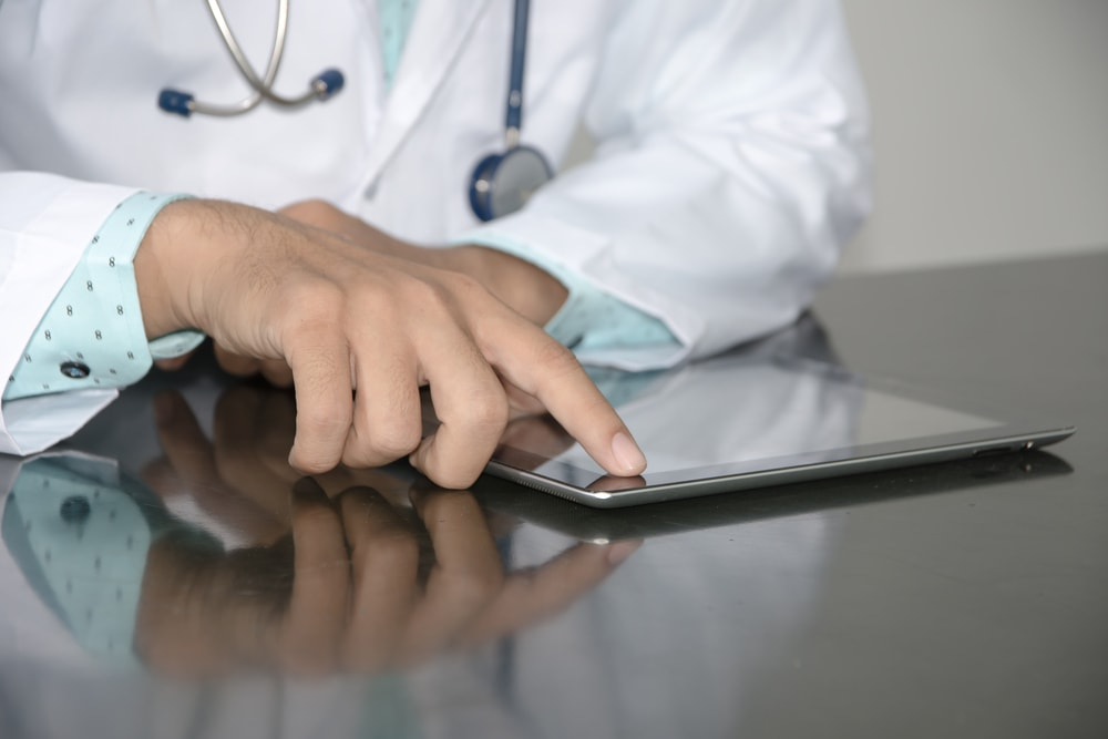 doctor touching tablet on desk