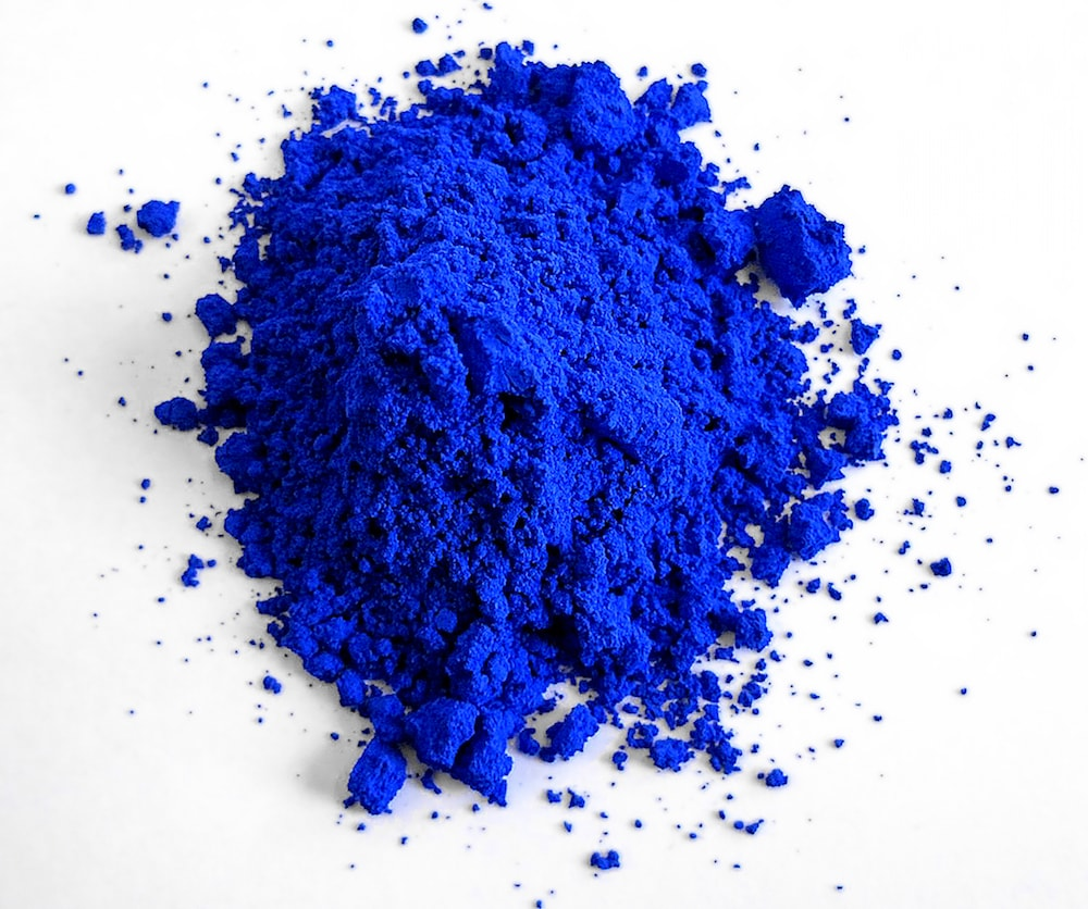 vibrant blue powder on a white background