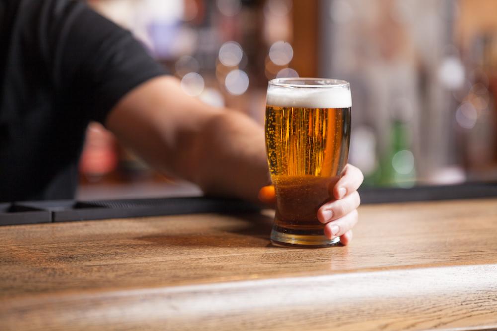 bartender pushing glass of beer across the bar