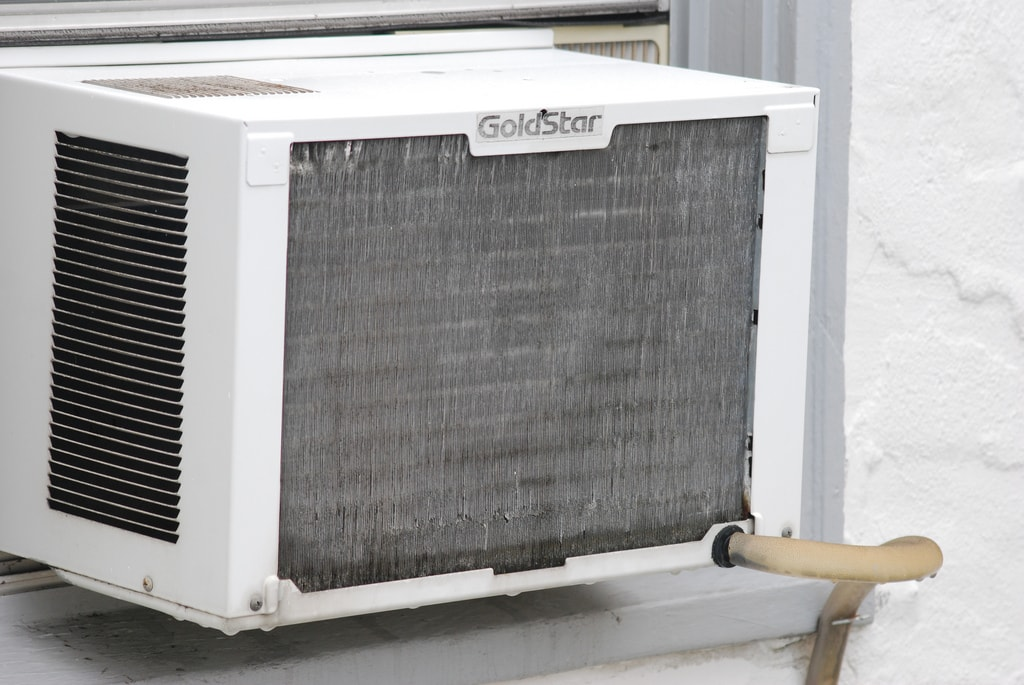 a dirty old air conditioner in a window