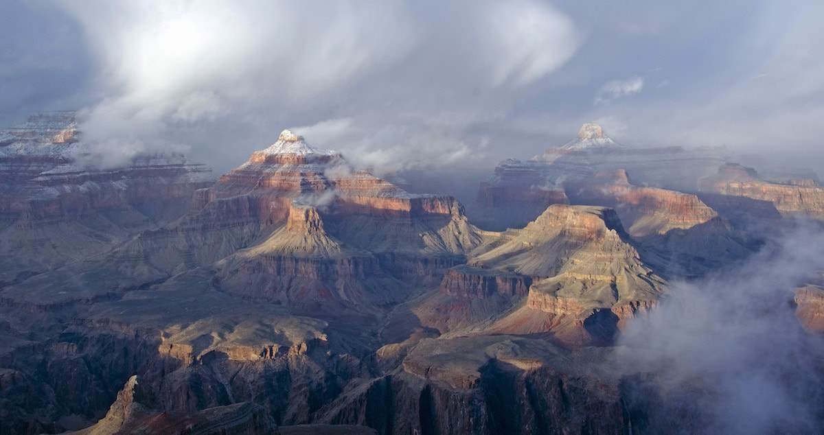 a real photo of the grand canyon with some of the peaks covered in snow on a grey cloudy day