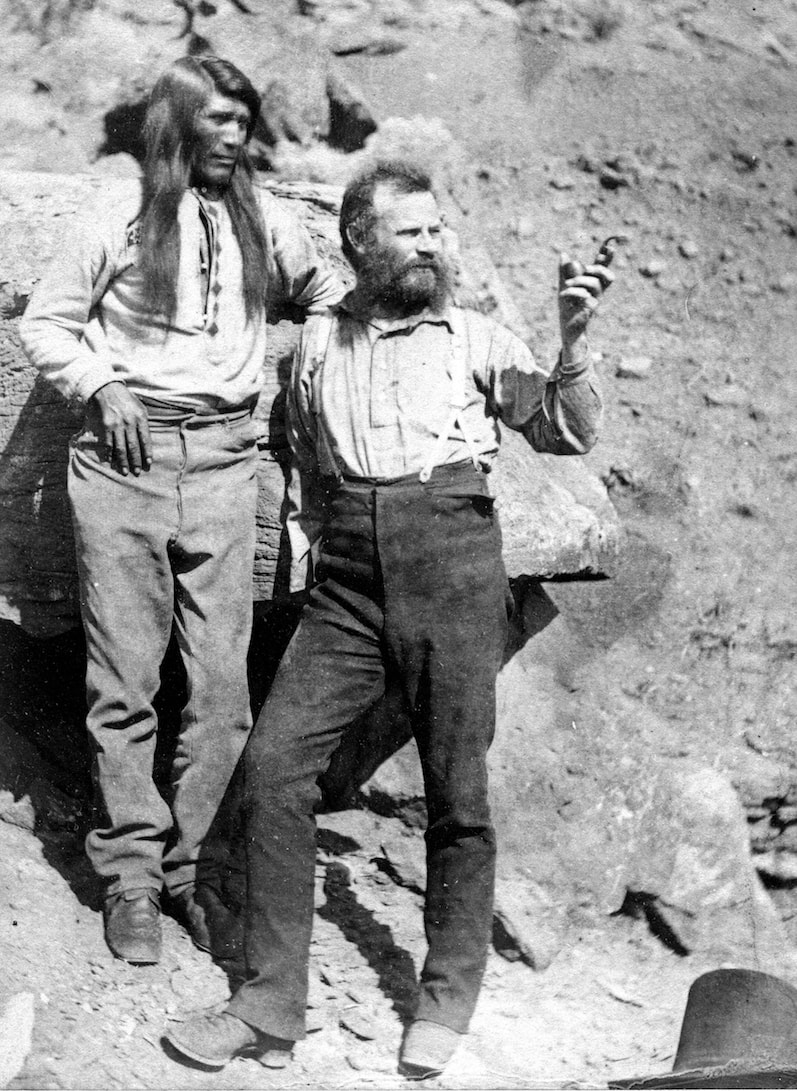 a black and white photograph of two men standing next to each other against a rock, one bearded (powell) pointing his finger ahead of him