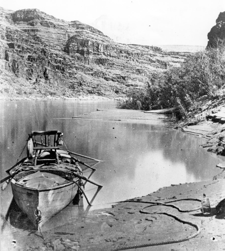 a closer view of powell's boat with the chair strapped to it, docked on the shore of the river