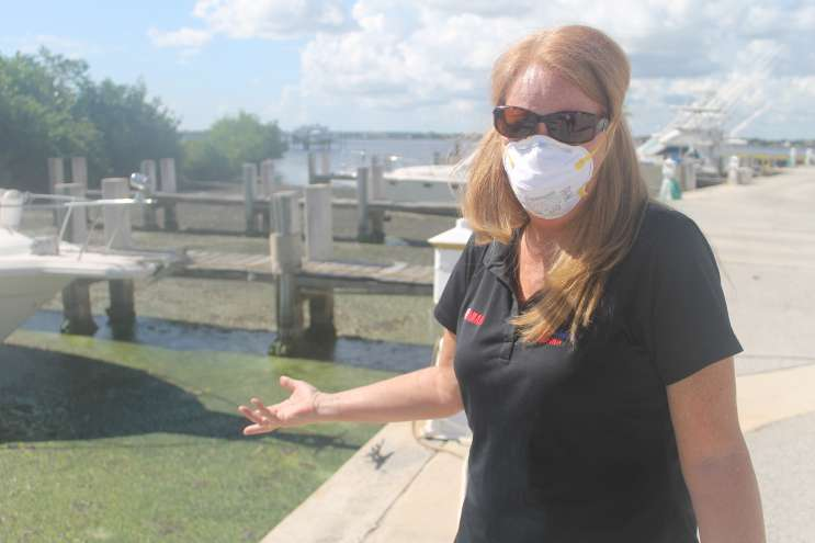 woman on pier with sunglasses and surgical mass gesturing to a lake with algae