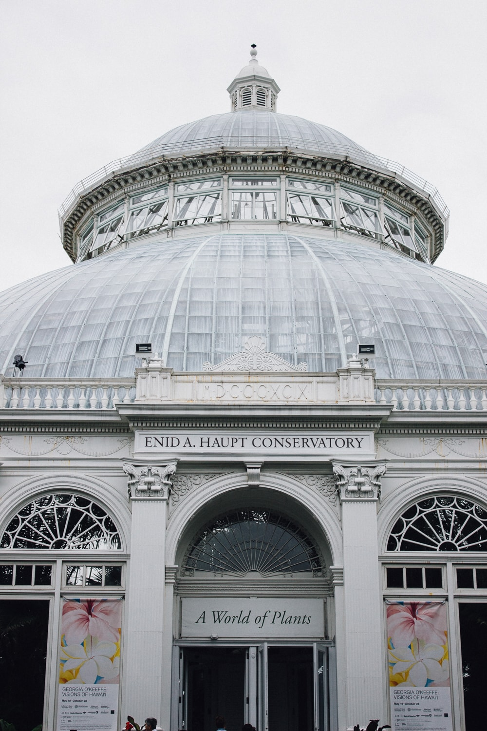 "The exterior of a greenhouse with a domed glass roof. above the front entrance it says ""enid a. haupt conservatory"" and ""a world of plants"""