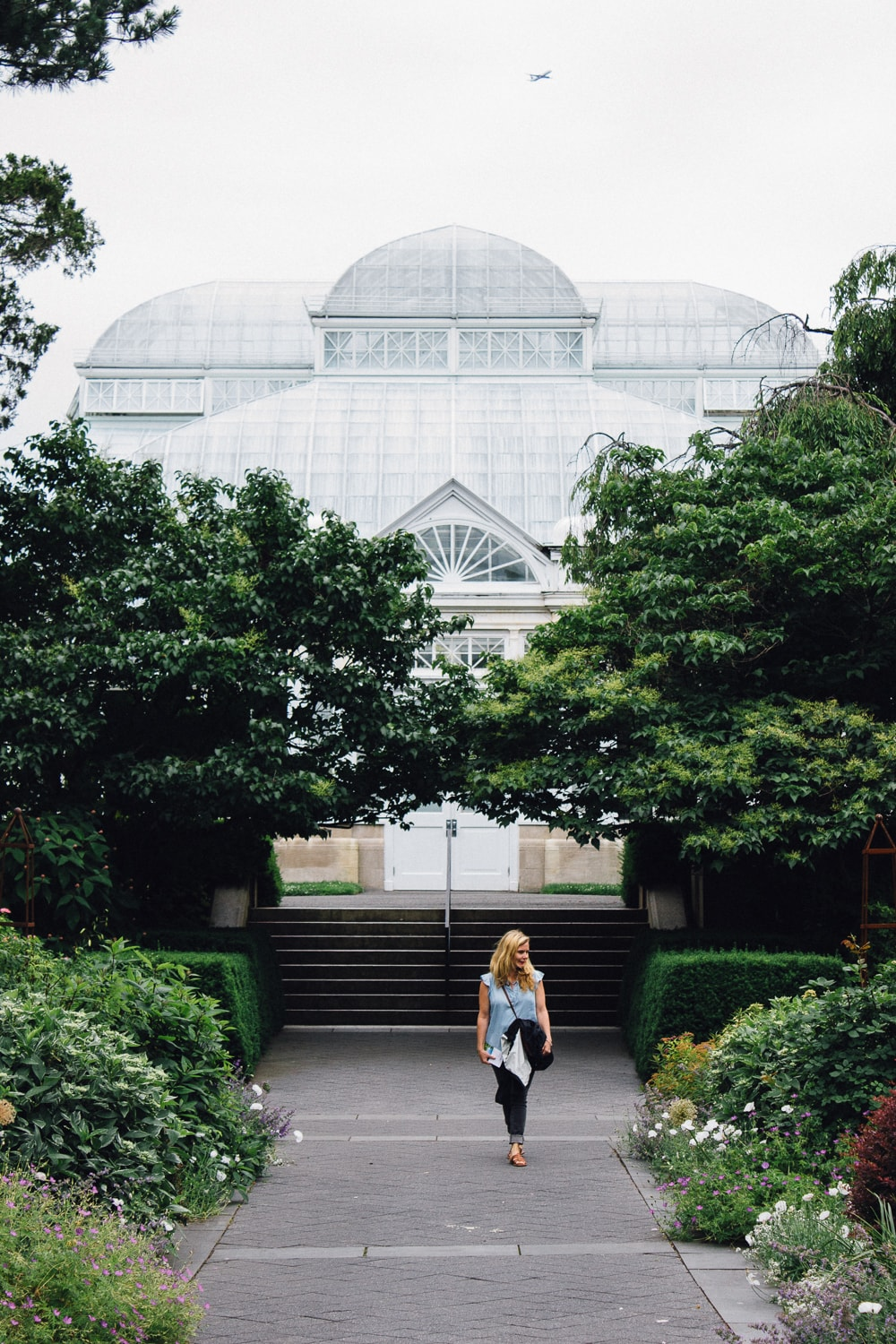 woman walking among gardens with greenhouse behind her