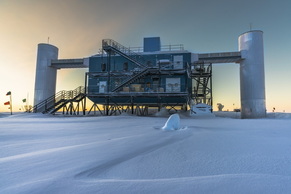 an isolated station out in a snowy field of antarctica at sunset